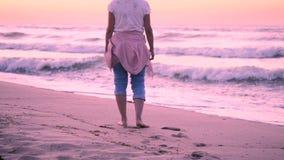 Ein Mädchen in den Blue Jeans und eine rosa Jacke, die auf ihrem Gurt gebunden wurde, kamen zum Meer stock footage