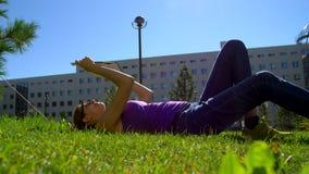 Ein Mädchen in den Gläsern liest ein Buch, das auf einem Gras sitzt stock footage
