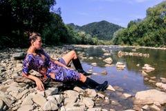 Ein Mädchen in den schwarzen Stiefeln steht in der Natur still Stockfotos