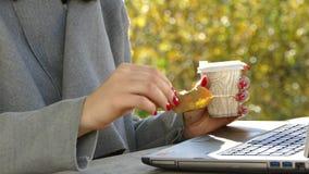 Ein Mädchen in der Natur sitzt mit einem Laptop und trinkt Kaffee stock video