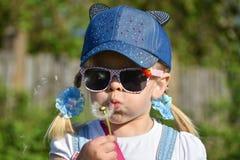 Ein Mädchen in der Sonnenbrille auf dem Gebiet brennt stark an einem Blumenlöwenzahn, Nahaufnahme, Sommer durch Lizenzfreie Stockfotos