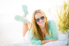 Jugendlich Mädchen, das auf den Strand legt lizenzfreies stockbild