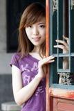 Ein Mädchen durch das alte Fenster. Lizenzfreies Stockbild
