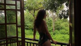 Ein Mädchen in einem Badeanzug in einem Bungalow stock video