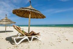 Ein Mädchen in einem Bikini ein Sonnenbad nehmend auf einem deckchair unter einem Regenschirm O lizenzfreies stockbild