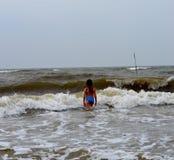 Ein Mädchen in einem blauen Badeanzug auf dem Yellow Sea stockfotos
