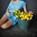 Ein Mädchen in einem blauen Kleid sitzt nahe bei einem Metallbecken mit gelben Tulpen stockbilder