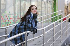 Ein Mädchen in einem blauen Mantel geht im Frühjahr auf Schnee und Wasser Lizenzfreie Stockfotografie
