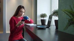 Ein Mädchen in einem Café steht im Internet über Telefon in Verbindung stock video footage