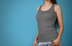 Ein Mädchen in einem grauen einfachen T-Shirt Leeres Trägershirt nahaufnahme isolat stockbilder