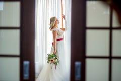 Ein Mädchen in einem Heiratskleid mit Make-up und Frisur steht in einem hellen Hotelzimmer nahe dem Fenster und untersucht heraus stockbild