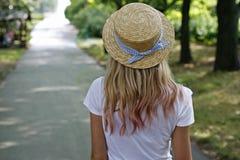 Ein Mädchen in einem Hut auf einem Weg Stockfoto