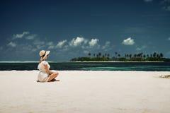 Ein Mädchen in einem Hut, der auf dem Strand sitzt maldives Weißer Sand Stockfoto