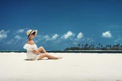 Ein Mädchen in einem Hut, der auf dem Strand sitzt maldives Weißer Sand Stockfotos