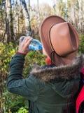 Ein Mädchen in einem Hut in einem Herbstwald trinkt Wasser von einer Flasche lizenzfreie stockbilder