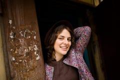 Ein Mädchen in einem Hut lächelt am Ausgang vom Haus Stockfotografie