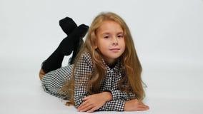 Ein Mädchen in einem karierten Kleid liegt auf dem Boden und leicht lächelt an der Kamera stock video
