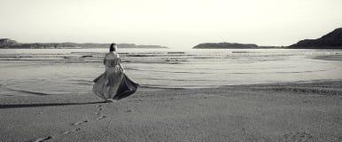 Ein Mädchen in einem Kleid steht das Meer bereit Lizenzfreie Stockfotografie