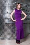 Ein Mädchen in einem langen purpurroten Kleid im Kleidungsshop Lizenzfreie Stockbilder