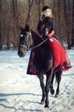 Ein Mädchen in einem langen schwarzen Kleid mit einem dunklen Pferd Stockfoto