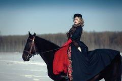 Ein Mädchen in einem langen schwarzen Kleid mit einem dunklen Pferd Stockfotografie