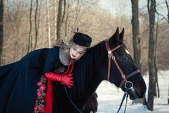 Ein Mädchen in einem langen schwarzen Kleid mit einem dunklen Pferd Stockbild