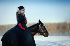 Ein Mädchen in einem langen schwarzen Kleid mit einem dunklen Pferd Stockfotos