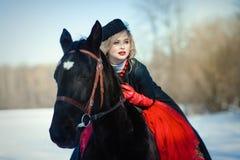 Ein Mädchen in einem langen schwarzen Kleid mit einem dunklen Pferd Lizenzfreies Stockfoto