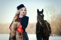 Ein Mädchen in einem langen schwarzen Kleid mit einem dunklen Pferd Stockbilder