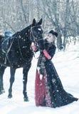 Ein Mädchen in einem langen schwarzen Kleid mit einem dunklen Pferd Lizenzfreies Stockbild