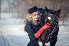 Ein Mädchen in einem langen schwarzen Kleid mit einem dunklen Pferd Lizenzfreie Stockfotos