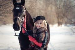 Ein Mädchen in einem langen schwarzen Kleid mit einem dunklen Pferd Lizenzfreie Stockbilder