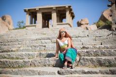 Ein Mädchen in einem Mantel sitzt auf Steinschritten Stockfotografie