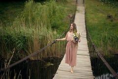 Ein Mädchen in einem Pfirsich-farbigen Kleid gehend in ein Dorf auf einer hölzernen hängenden Brücke mit einem Blumenstrauß von B lizenzfreie stockfotos