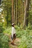 Ein Mädchen in einem Poncho und in einem Hut im Wald Stockfoto