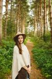 Ein Mädchen in einem Poncho und in einem Hut im Wald Lizenzfreie Stockfotografie