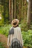 Ein Mädchen in einem Poncho und in einem Hut im Wald Stockfotografie
