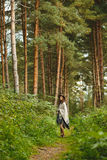 Ein Mädchen in einem Poncho und in einem Hut im Wald Lizenzfreies Stockbild