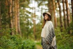 Ein Mädchen in einem Poncho und in einem Hut im Wald Stockfotos