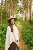 Ein Mädchen in einem Poncho und in einem Hut im Wald Stockbild