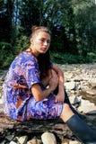 Ein Mädchen in einem purpurroten Kleid sitzt auf den Steinen Stockfoto