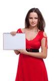 Ein Mädchen in einem roten Kleid hält ein Notizbuch an Stockfoto