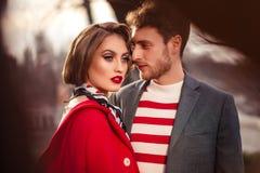 Ein Mädchen in einem roten Mantel mit einem Mann stockfoto