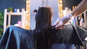 Ein Mädchen in einem Schönheitssalon mit einem Friseur Das Konzept der Haarpflege im Salon, Keratin, Haargeraderichten stock video footage
