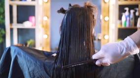 Ein Mädchen in einem Schönheitssalon mit einem Friseur Das Konzept der Haarpflege im Salon, Keratin, Haargeraderichten stock footage
