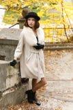 Ein Mädchen in einem schwarzen Hut und in einem Mantel steht in einem Herbstpark und schaut oben retro draußen stockbilder