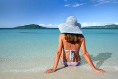 Ein Mädchen in einem Sommerhut, der auf dem Sand und dem Blick am Himmel auf einem Hintergrund liegt Lizenzfreie Stockfotografie