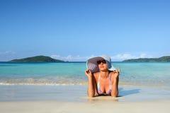 Ein Mädchen in einem Sommerhut, der auf dem Sand und dem Blick am Himmel liegt Lizenzfreies Stockfoto