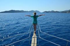 Ein Mädchen in einem Strohhut auf dem Bogen der Yacht streckte Arme aus stockbild