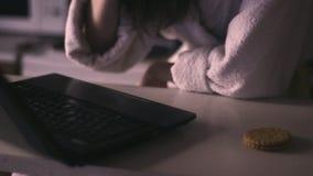 Ein Mädchen in einem trinkenden Kaffee des Bademantels und Arbeiten an dem netbook stock footage